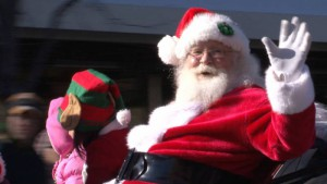 Santa rides on a float and waves in the Olde Golden Christmas Parade