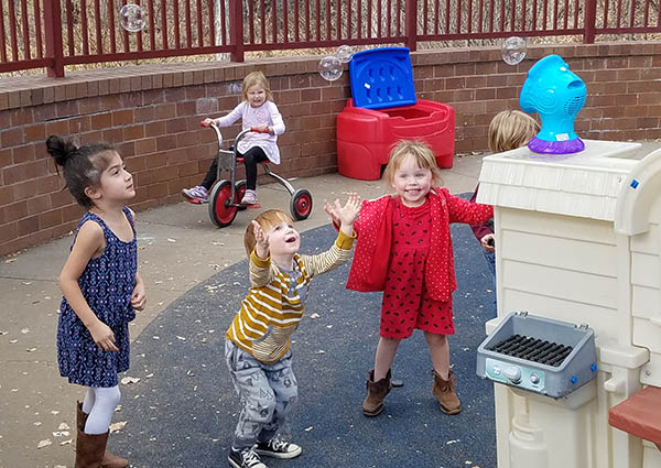 Preschool children play with bubbles