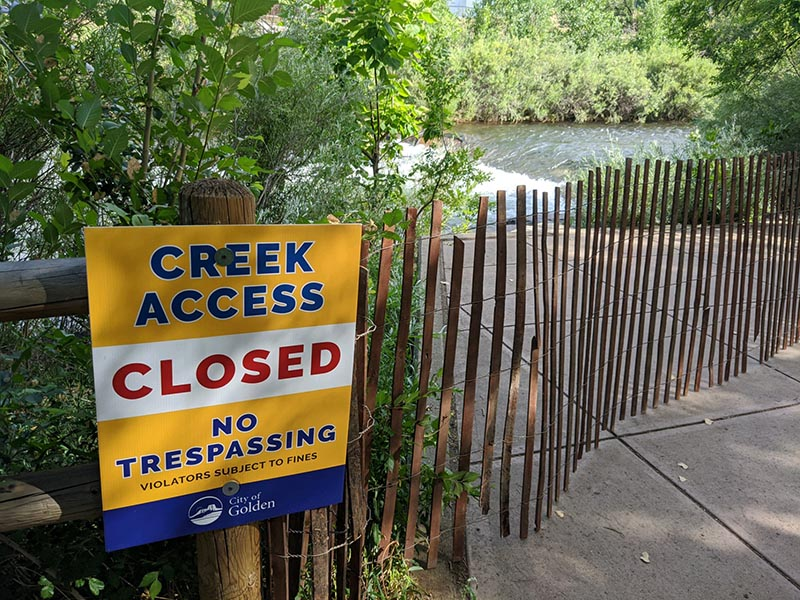 A sign marking that creek access is closed along with fencing.