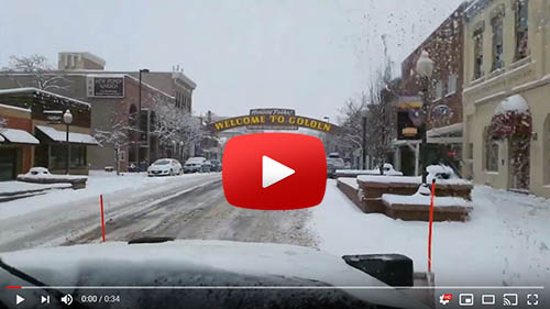 Still of a snowy street from the snow plow video and play button.